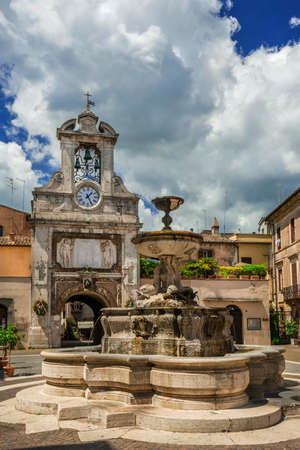 Sutri main square in the historic city center with fountain, old clock tower and clouds Éditoriale