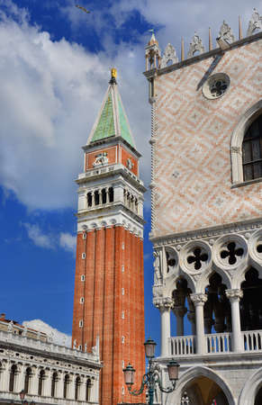 Saint Mark bell tower with golden angel at the top with blue sky and clouds, in the center of Venice