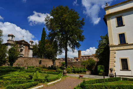 Villa Savorelli public park in the ancient medieval town of Sutri, with old church and beautiful clouds