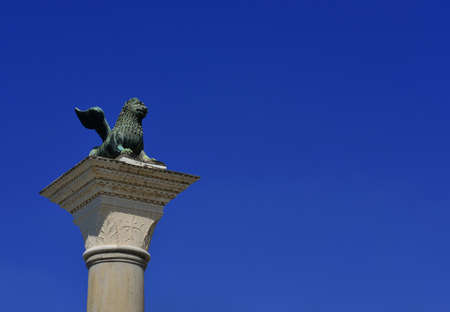 Saint-Marc Lion ancienne statue de bronze au sommet de la colonne médiévale, érigée en 1172. Symbole de l'ancienne République de Venise (avec ciel bleu et espace copie)