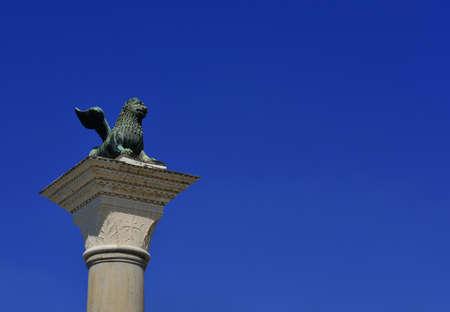 Saint-Marc Lion ancienne statue de bronze au sommet de la colonne médiévale, érigée en 1172. Symbole de l'ancienne République de Venise (avec ciel bleu et espace copie) Banque d'images - 82823485