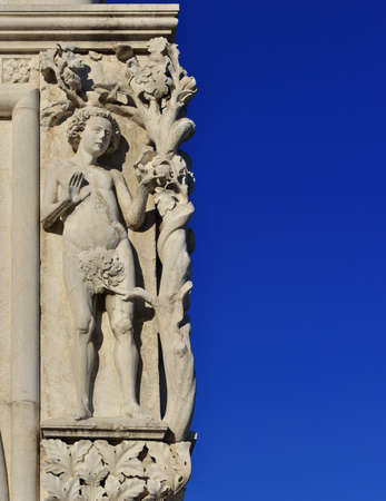 Adam le poing humain dans le jardin d'Eden et le péché originel, une sculpture médiévale à la place Saint-Marc, à Venise (avec copie) Banque d'images - 84961990