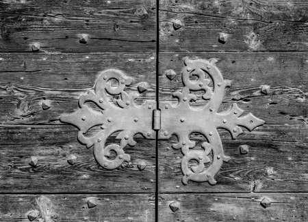 Ancienne charnière en fer sur une porte en bois usée (noir et blanc) Banque d'images