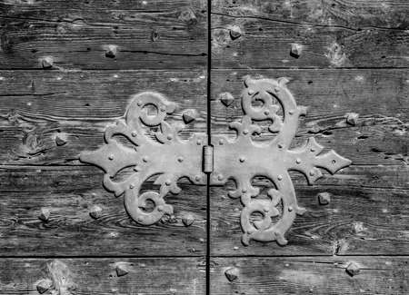 Old iron hinge on a worn wooden door (Black and White)