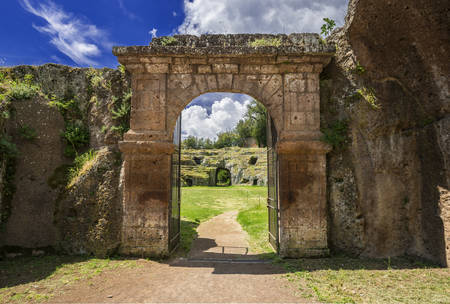 Ancient roman stone amphitheater main gate in the town of Sutri with clouds, near Rome