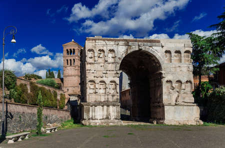 The so called Arch of Janus ruins with old church bell tower in the center of Rome
