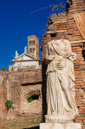 Vestal pagan temple with ancient statue and christian church in the Roman Forum ruins