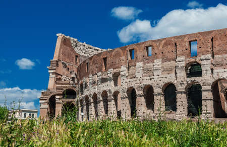 Coliseum inner ring monumental arcade in the center of Rome with green grass and blue sky