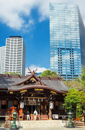 Tokyo, Japan, October 8, 2017: Tradition and Modernity in Japan. People pray in an old temple under modern skyscrapers in Tokyo. Éditoriale