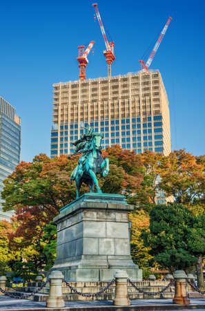 Tokyo, Japan, November 6, 2017: Tradition and Modernity, Past and Future in Tokyo. Modern skyscraper is under construction behind an old samurai warrior statue surrounded by autumn leaves in the city center. Éditoriale
