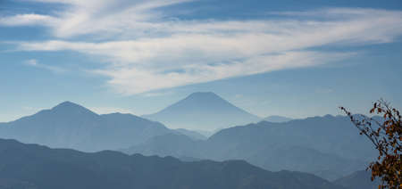 Iconic Mount Fuji wrapped in misty clouds like and old painting, seen from Mount Takao in Japan