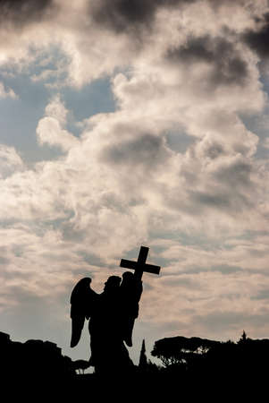 Ange tenant la silhouette de la statue de Sainte Croix avec un beau ciel au coucher du soleil et espace copie. Un chef-d'?uvre baroque du XVIIe siècle au sommet du pont Saint-Ange au centre de Rome Banque d'images