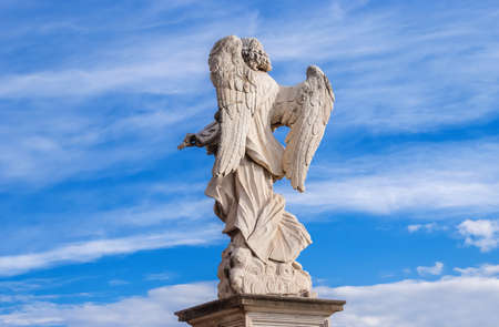Angel marble statue  with beautiful clouds. A 17th centuty baroque masterpiece at the top of SantAngelo Bridge in the center of Rome