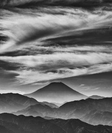 L'emblématique Mont Fuji enveloppé de nuages ??brumeux et de peinture ancienne, vu du Mont Takao au Japon (Noir et Blanc)