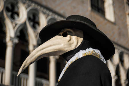 Plague Doctor Mask, traditional venetian costume of Venice Carnival, with Doge Palace gothic decoration in the background