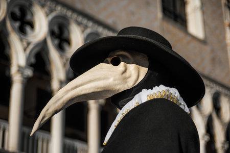 Maska Plague Doctor, tradycyjny wenecki strój karnawału w Wenecji, z gotycką dekoracją Pałacu Dożów w tle