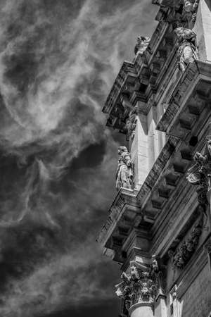 Detail of the 17th century baroque facade of San Salvador Church (Holy Savior) in Venice with beautiful clouds (Black and White) Banque d'images