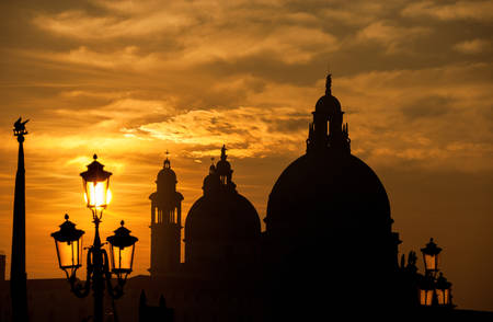 Venice sunset with Salute Basilica (Saint Mary of Health) baroque domes, lamp and Saint Mark Lion silhouette Banque d'images