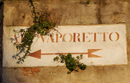 Vaporetto (venetian water bus) old road sign with plants on a wall in Venice Banque d'images