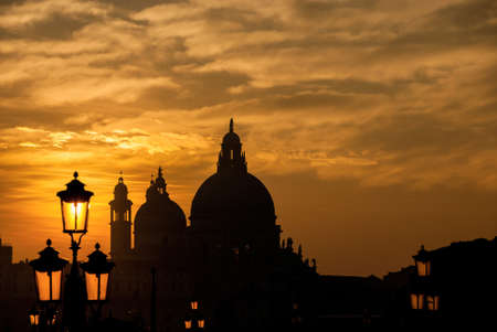 Venice sunset with Salute Basilica (Saint Mary of Health) baroque domes and lamps
