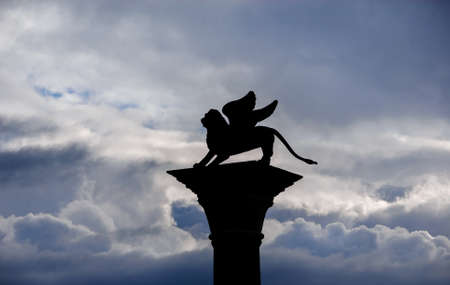 Saint Mark Winged Lion old medieval statue silhouette among clouds Banque d'images