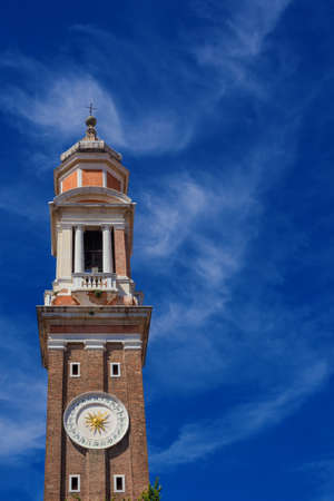 Church of the Holy Apostles of Christ baroque bell and clock tower among clouds in Venice (with copy space) Banque d'images