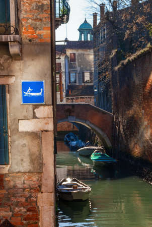 Venice characteristic canal with gondola water sign and a little bridge