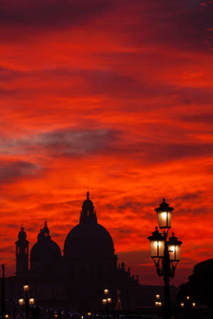 Red blood sky sunset over Venice Lagoon with Salute Basilica domes, Saint Mark Lion and lamps