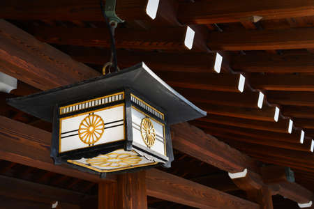 Old japanese lantern with chrysanthemum motif under a traditional wooden roof