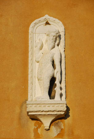 Monstrous primitive hairy man with club old medieval relief on a wall in Venice