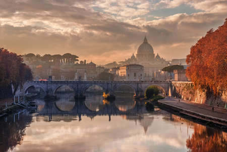 Autumn sunset over River Tiber with Saint Angel Bridge and Saint Peter Dome in the evening haze Banque d'images