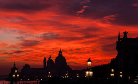 Red blood sky sunset over Venice Lagoon with Salute Basilica domes Saint Mark Lion and lamps