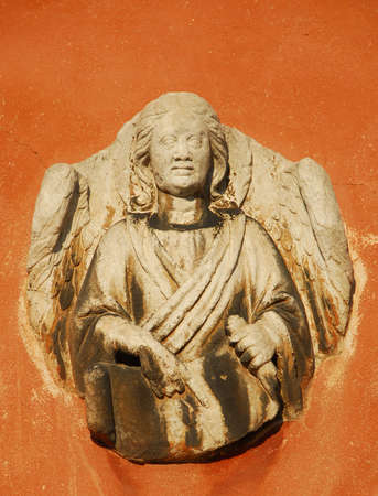 Angel holding a sacred scroll old relief on a Venice wall Stock Photo