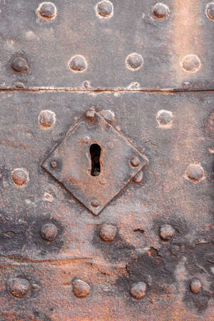 Very old iron keyhole on an iron door wiht studs and rust Stock Photo