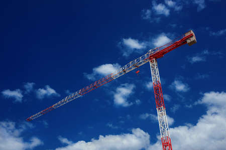 Red and white construction crane with blue sky and clouds 版權商用圖片