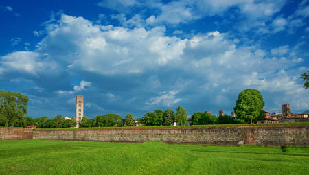 Panoramic view of Lucca historic center skyline with medieval towers seen from ancient walls public park