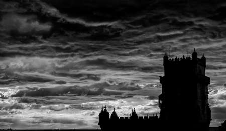 Panoramic view of Atlantic Ocean with ancient Belem Tower silhouette and dramatic sky at sunset, near Lisbon in Portugal (Black and White)