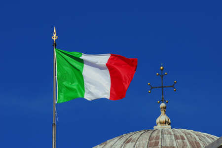 Religion and Politics in Italy. Italian National Flag fluttering in the wind close to a Christian cross