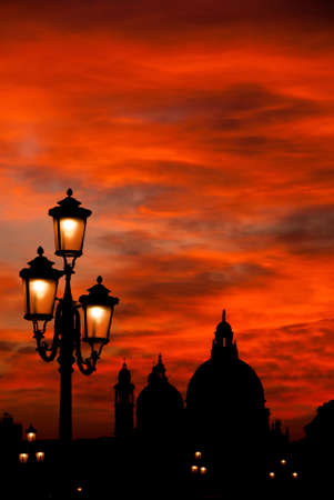Mysterious sunset over Salute Basilica (Saint Mary of Health) domes with old street lamps in Venice 写真素材