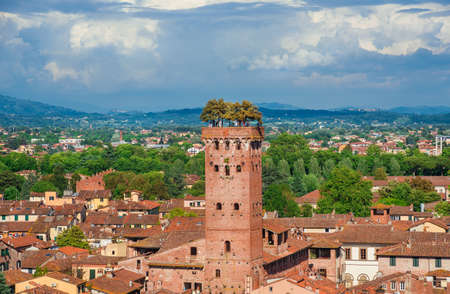 Lucca, Italy, May 10, 2018: The famous and characteristic medieval Guinigi Tower with oak trees and tourists at the top, erected in the 14th century in the historic city center