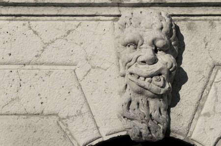 Grotesque in Venice. Bizarre monster guardian head on Santa Formosa Church bell tower (17th century)