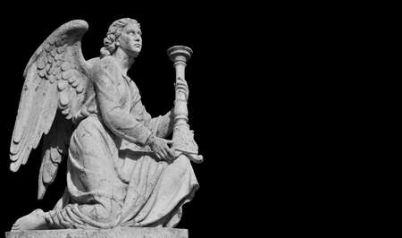 Kneeling angel with candlestick looks at the heaven. Marble statue at the top of St Roch Church in Rome, erected in 1832. (Black and White with copy space)