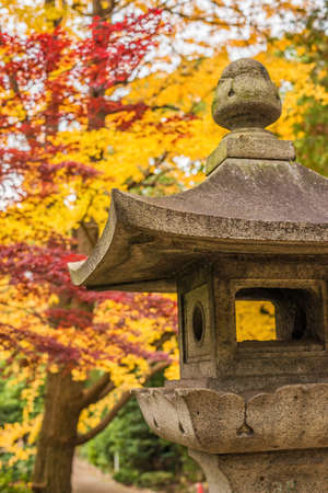 Autumn in Japan. Old traditional japanese stone lantern with red and yellow leaves in a park