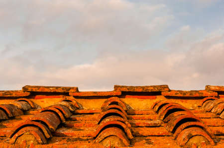 Old ceramic tiles roof with lichens and clouds above turn red at sunset as background (with copy space)