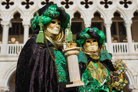 Venice, Italy, February 10, 2018: Carnival in Venice. Two beautiful Venetian masks with Saint Mark Lion in front of Doge Palace