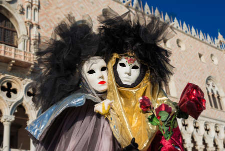 Venice, Italy, February 10, 2018: Carnival in Venice. Two beautiful Venetian masks with red roses in front of Doge Palace Editorial
