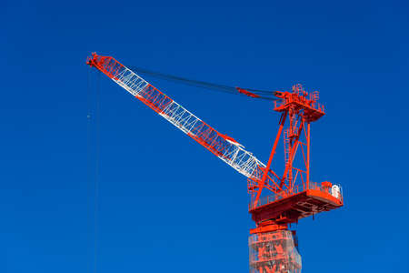 Construction fixed crane at work against a blue sky