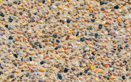 Concrete wall with colorful stones and gravel as background Reklamní fotografie