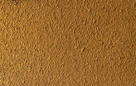 Golden concrete wall with rough surface as background