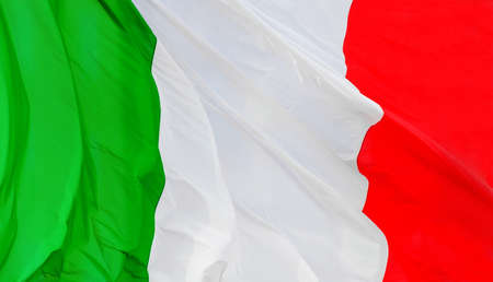 Tricolore (Three colors) Italian national flag fluttering in the wind as background